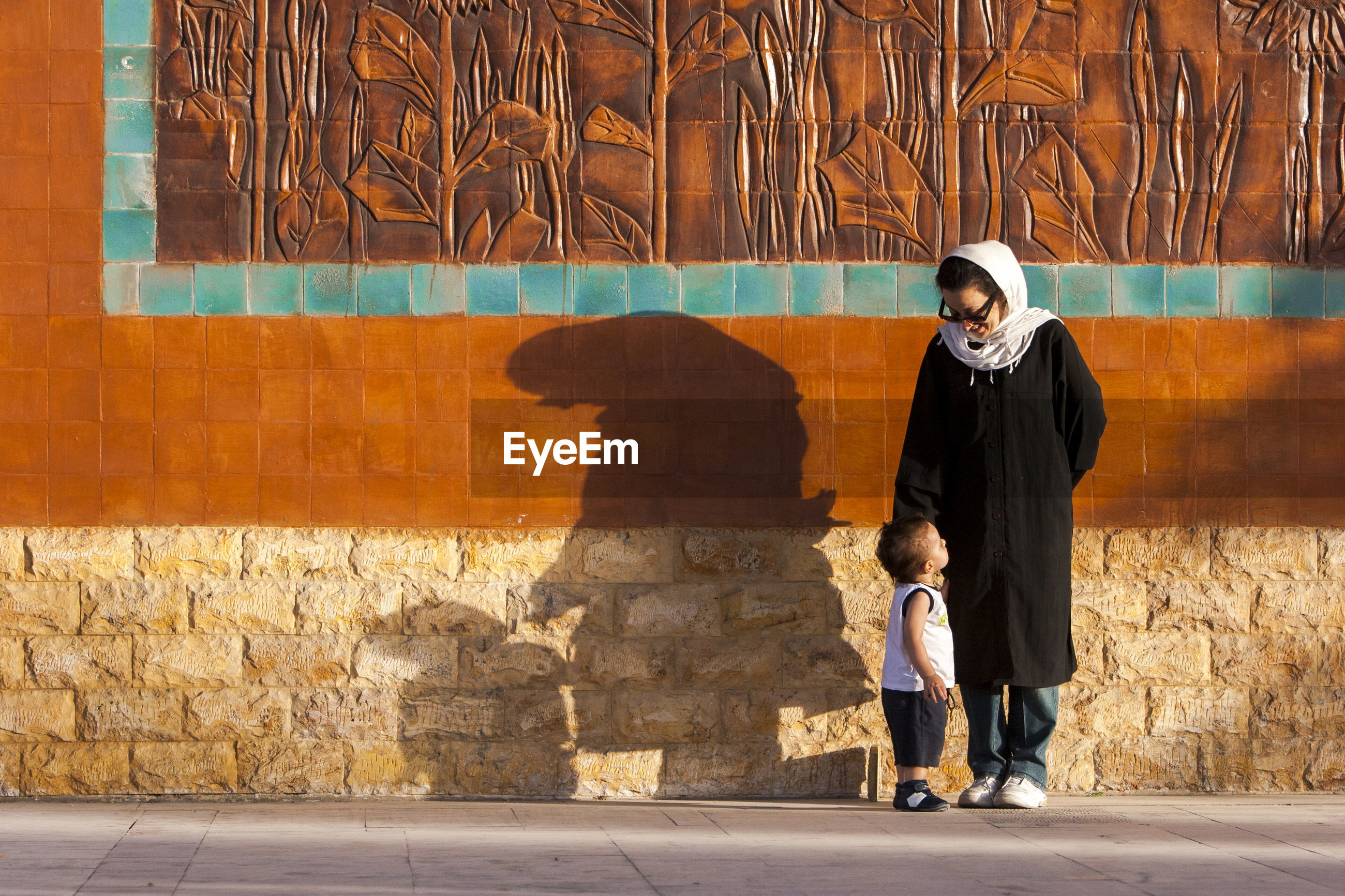 Mother with son standing on footpath against wall