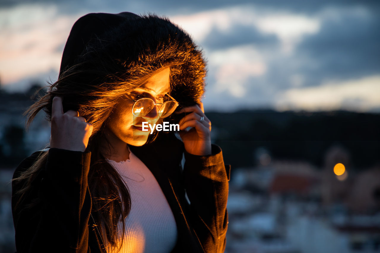 Young woman wearing hood standing outdoors during sunset