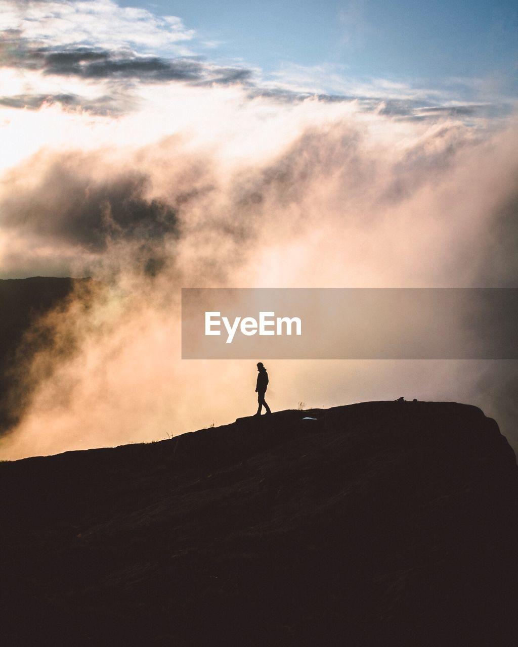 Silhouette Man Walking On Mountain Against Cloudscape