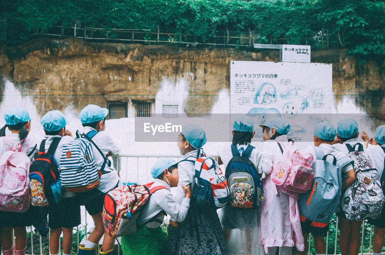 School Children Standing By Fountain In Park