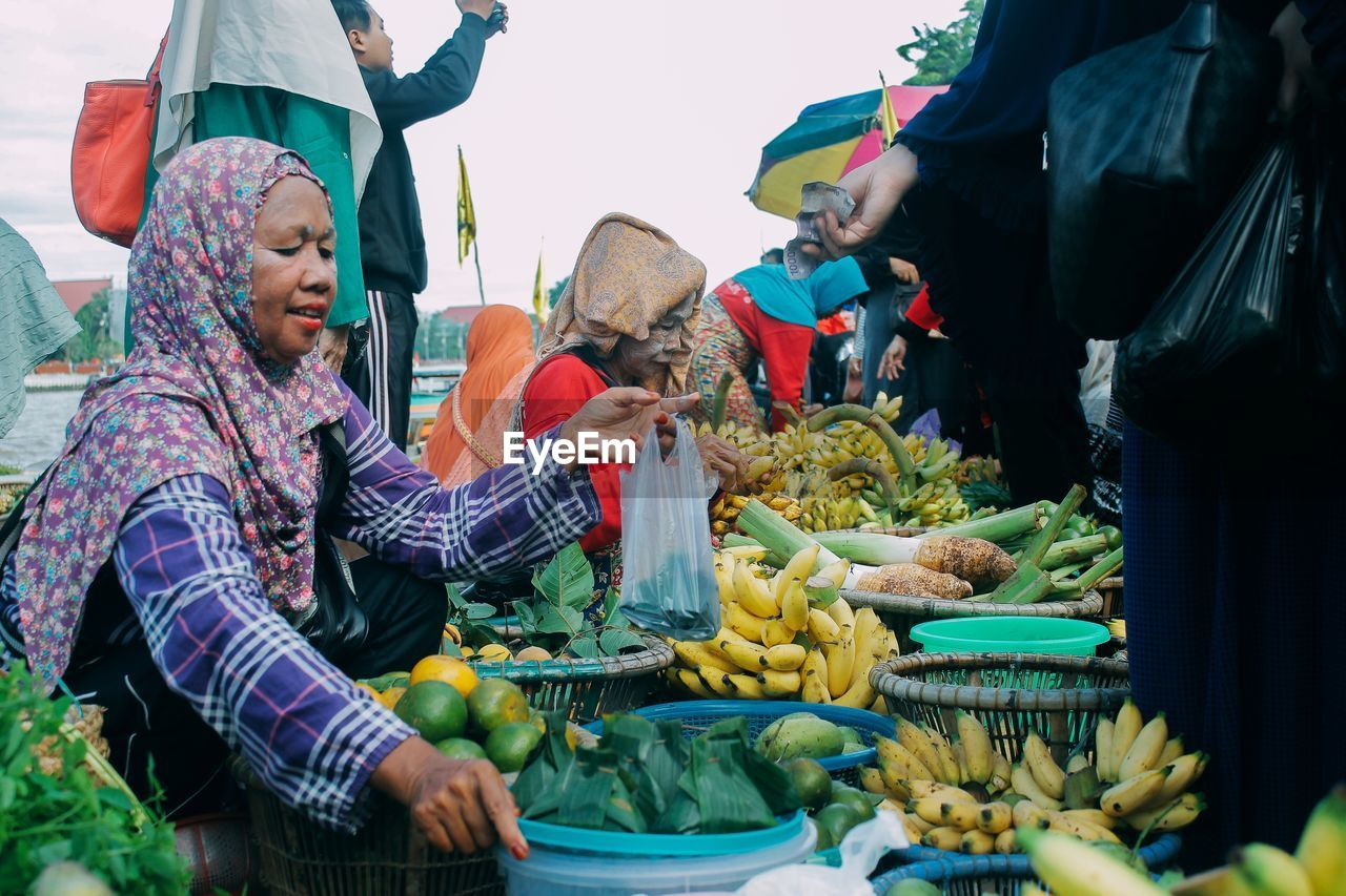 food and drink, market, retail, food, healthy eating, freshness, market stall, real people, group of people, men, business, wellbeing, selling, women, fruit, for sale, adult, small business, vegetable, people, vendor, buying, retail display, outdoors, sale, consumerism, street market