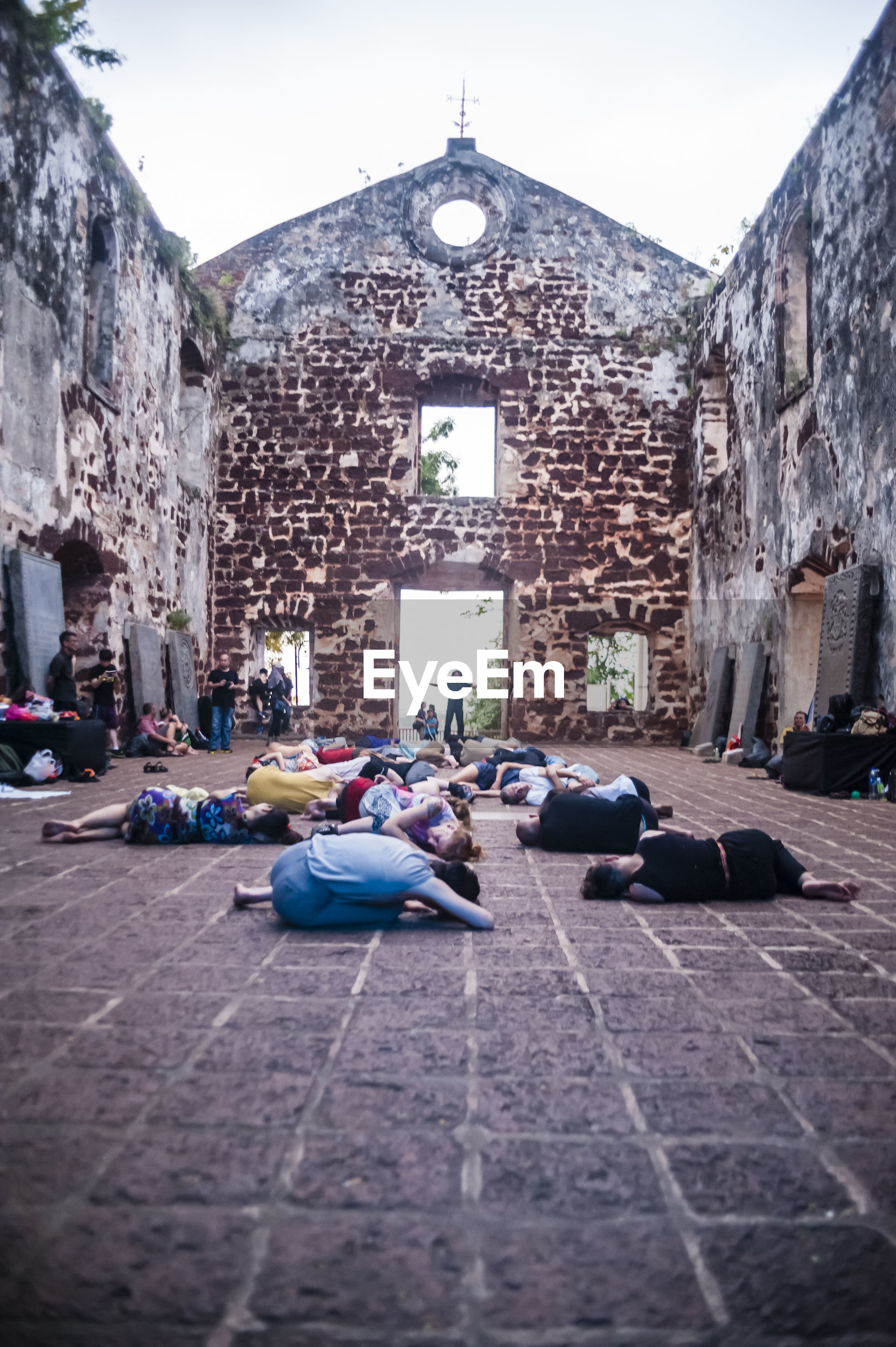 Choreographer and dancers lying on floor at historic building