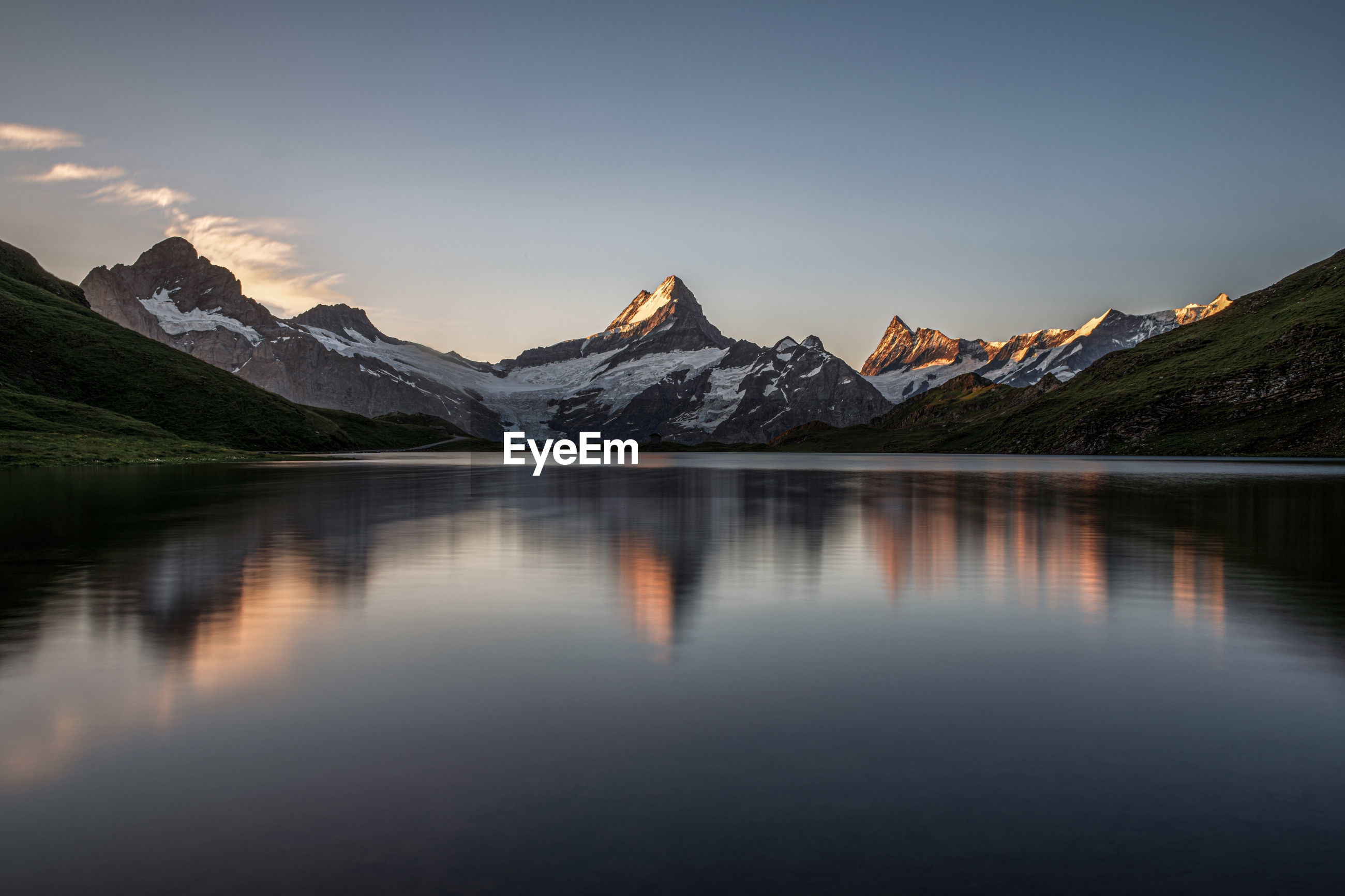 Scenic view of lake bachalpsee and the mountain schreckhorn against sky during dawn