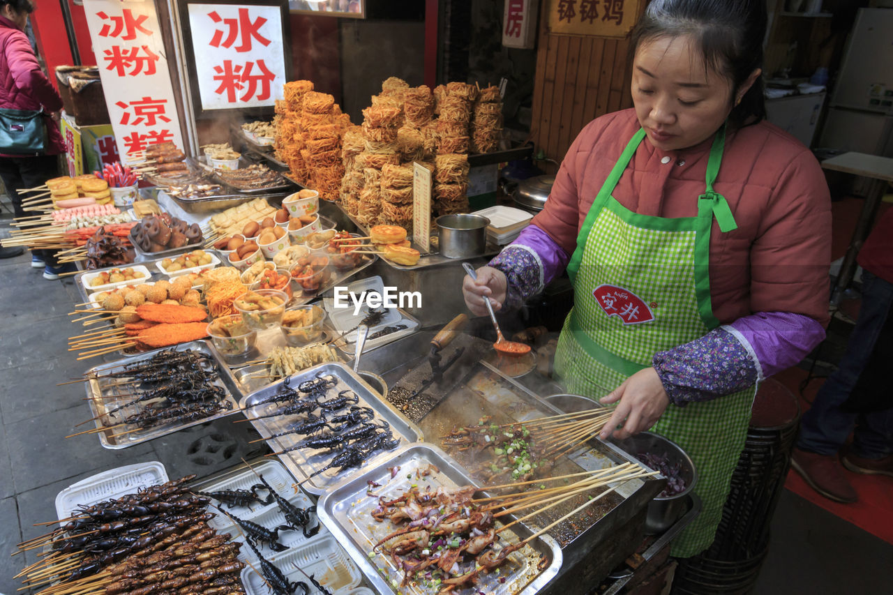 food, food and drink, real people, one person, childhood, females, women, casual clothing, market, retail, freshness, holding, child, business, standing, lifestyles, preparation, for sale, outdoors, preparing food, retail display, innocence