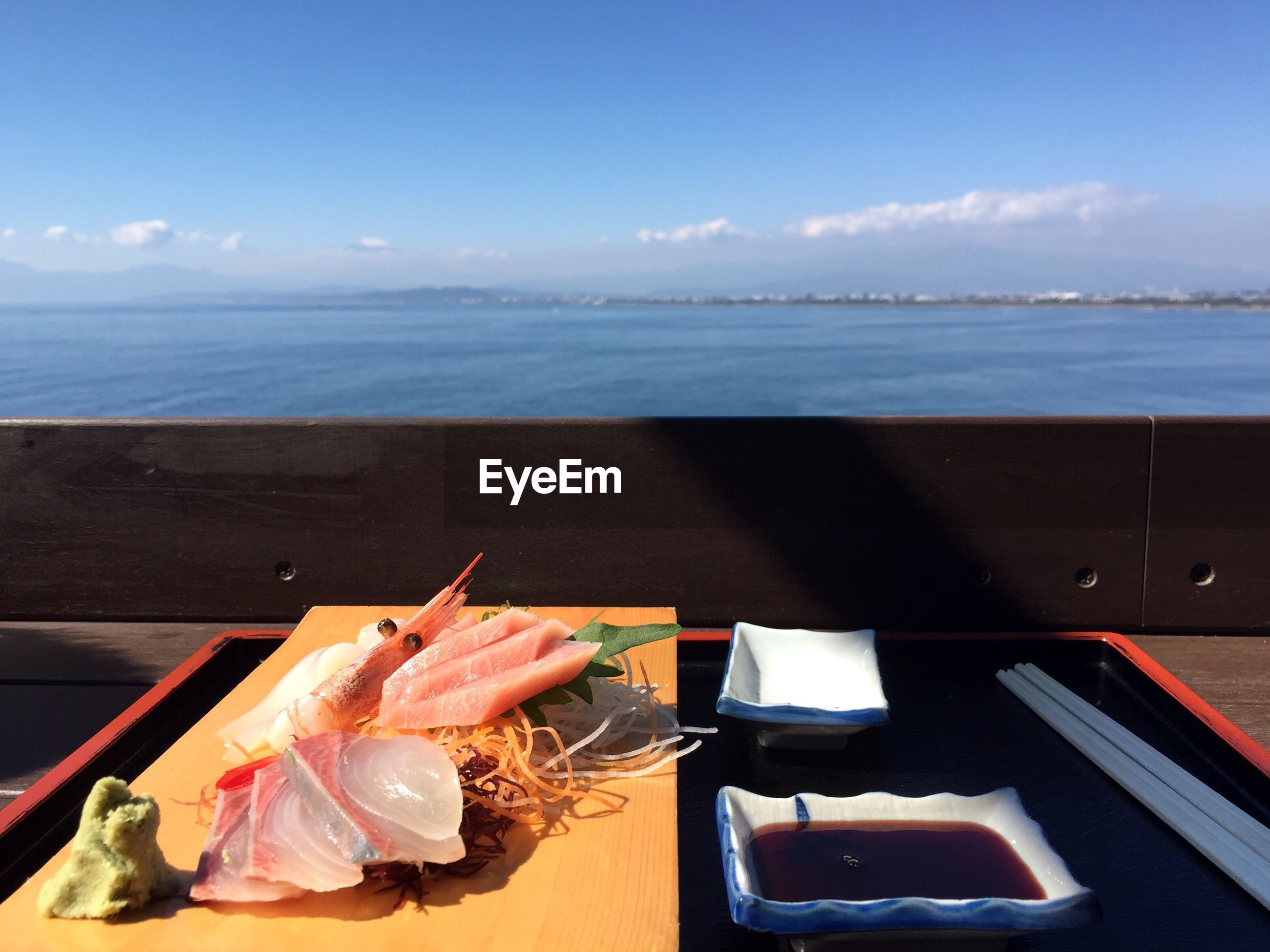 Close-up of seafood on table by sea against sky