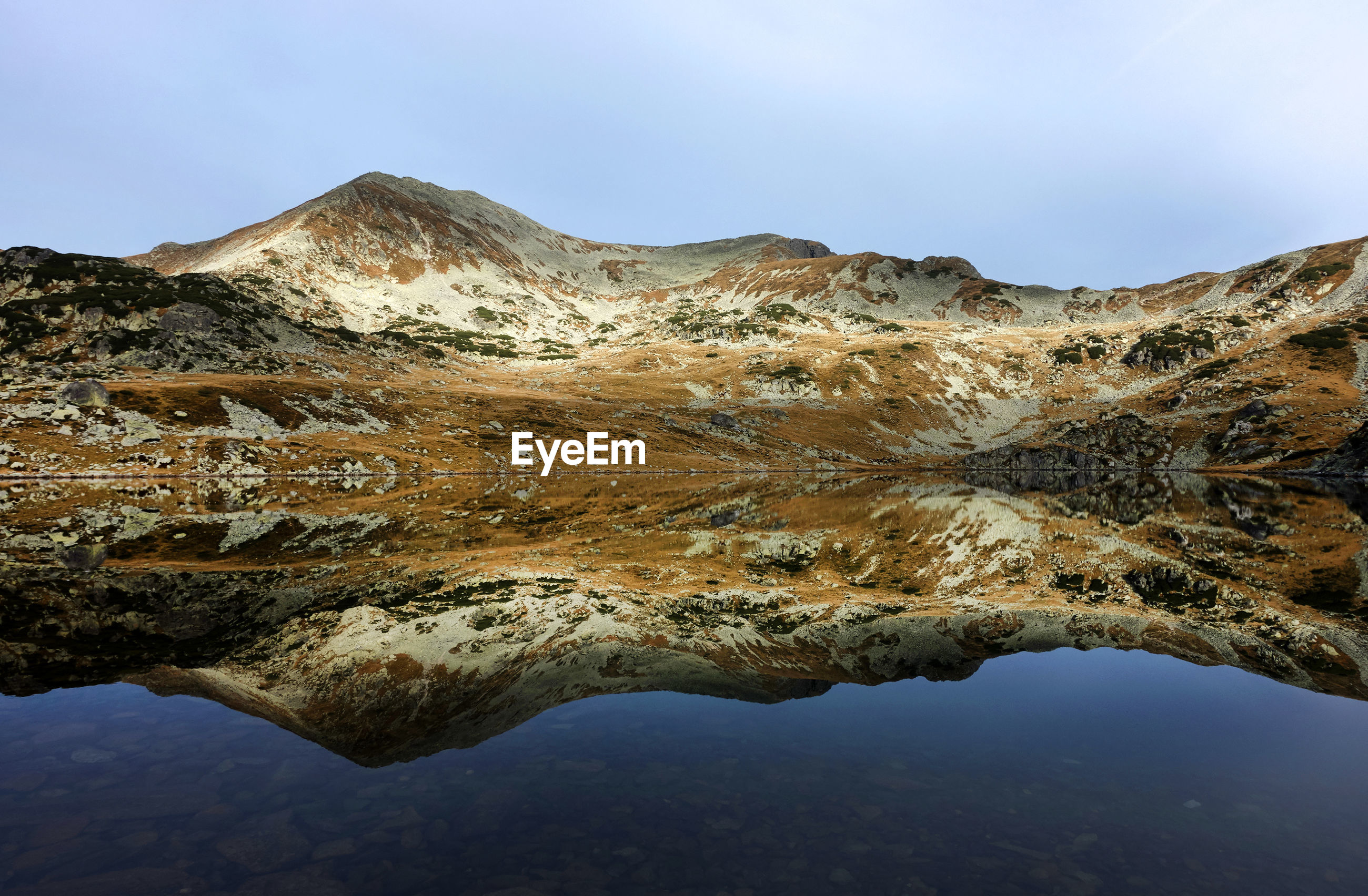 Idyllic shot of lake and mountains against sky