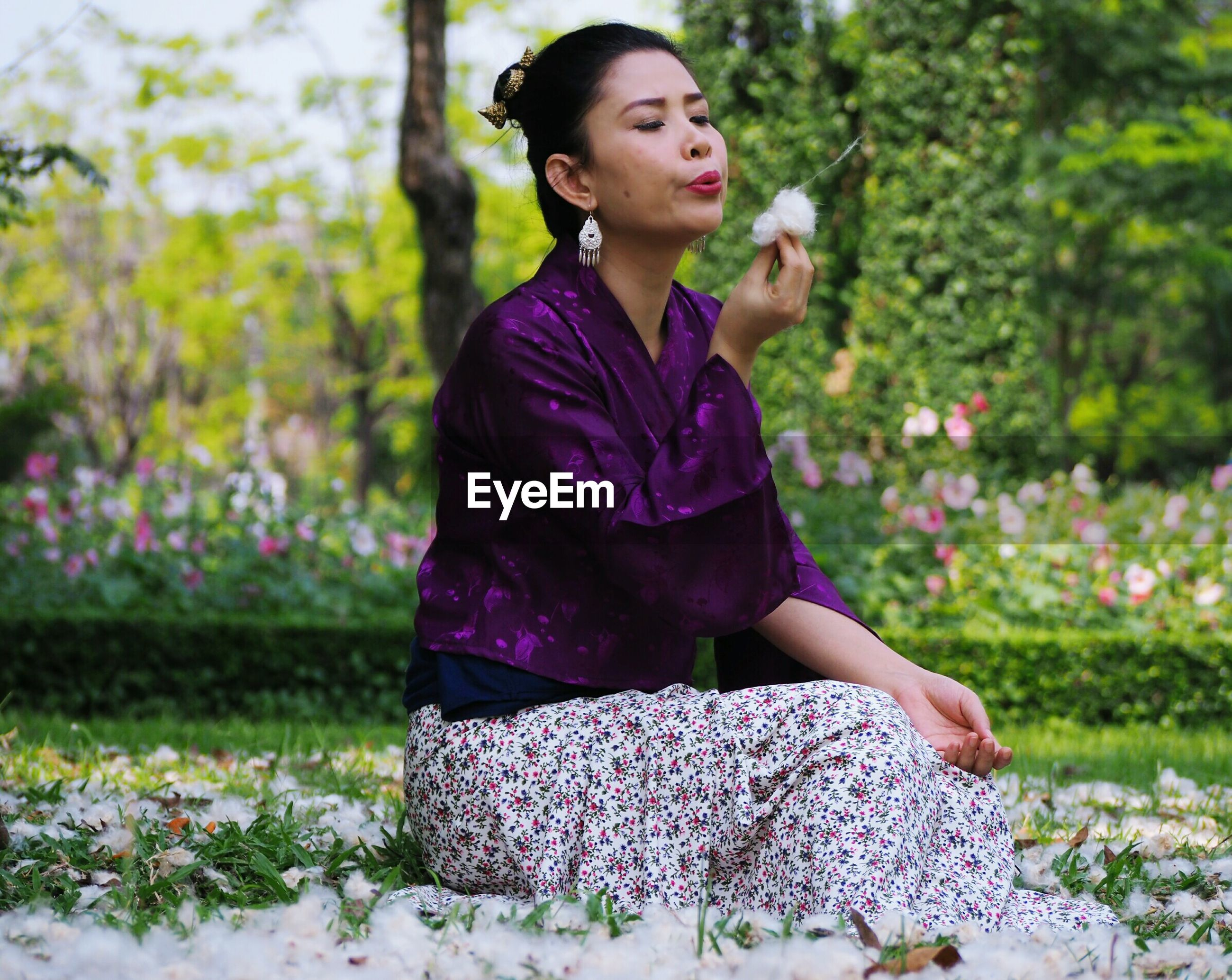 Woman blowing flower while sitting on field