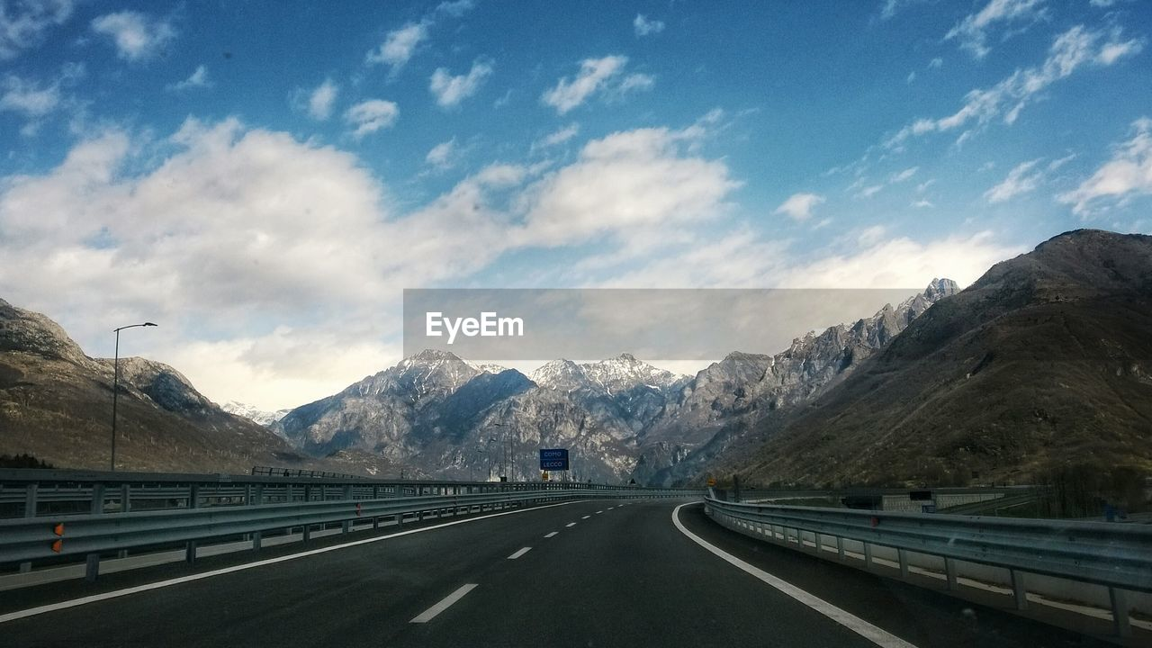 mountain, transportation, road, cloud - sky, sky, mountain range, sign, the way forward, symbol, mode of transportation, car, motor vehicle, direction, beauty in nature, scenics - nature, no people, land vehicle, road marking, marking, day, outdoors, crash barrier, snowcapped mountain