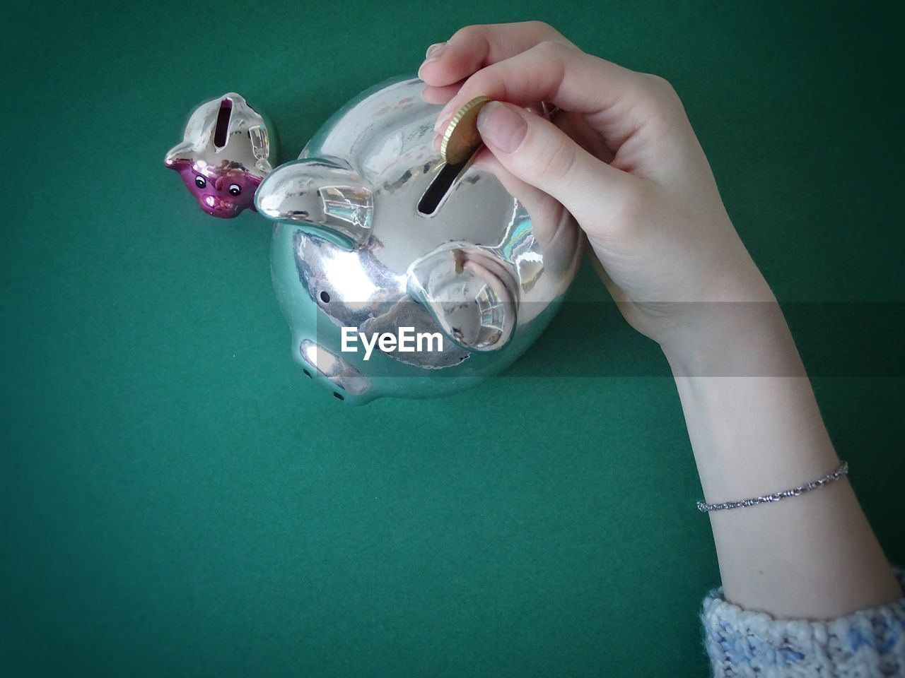 Cropped Hand Of Woman Putting Coin In Piggy Bank On Table