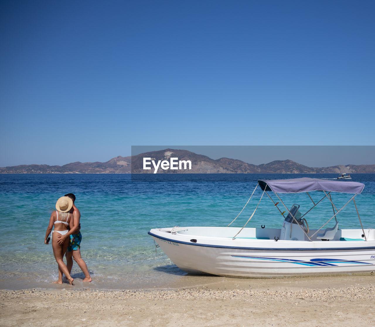 MAN AT BEACH AGAINST CLEAR BLUE SKY