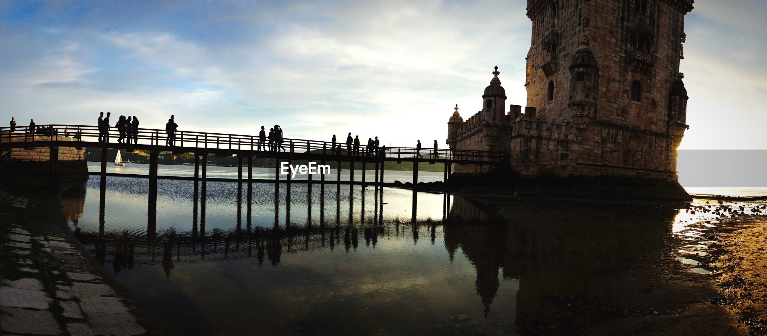 Silhouette tourist visiting belem tower against sky