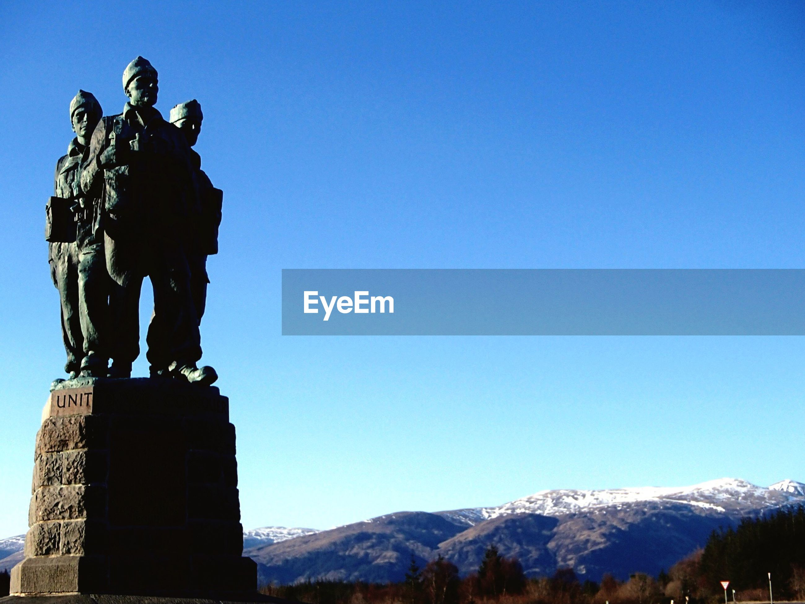 statue, mountain, clear sky, blue, copy space, sculpture, low angle view, human representation, tranquil scene, tranquility, mountain range, nature, scenics, beauty in nature, mountain peak, outdoors, tourism, monument, cliff, non-urban scene, high section