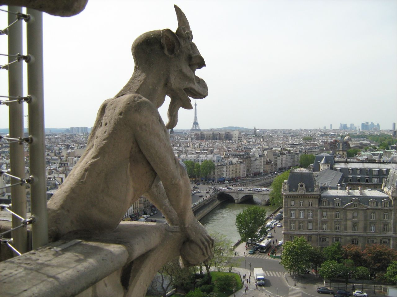 Gargoyle Statue With Cityscape Against Sky