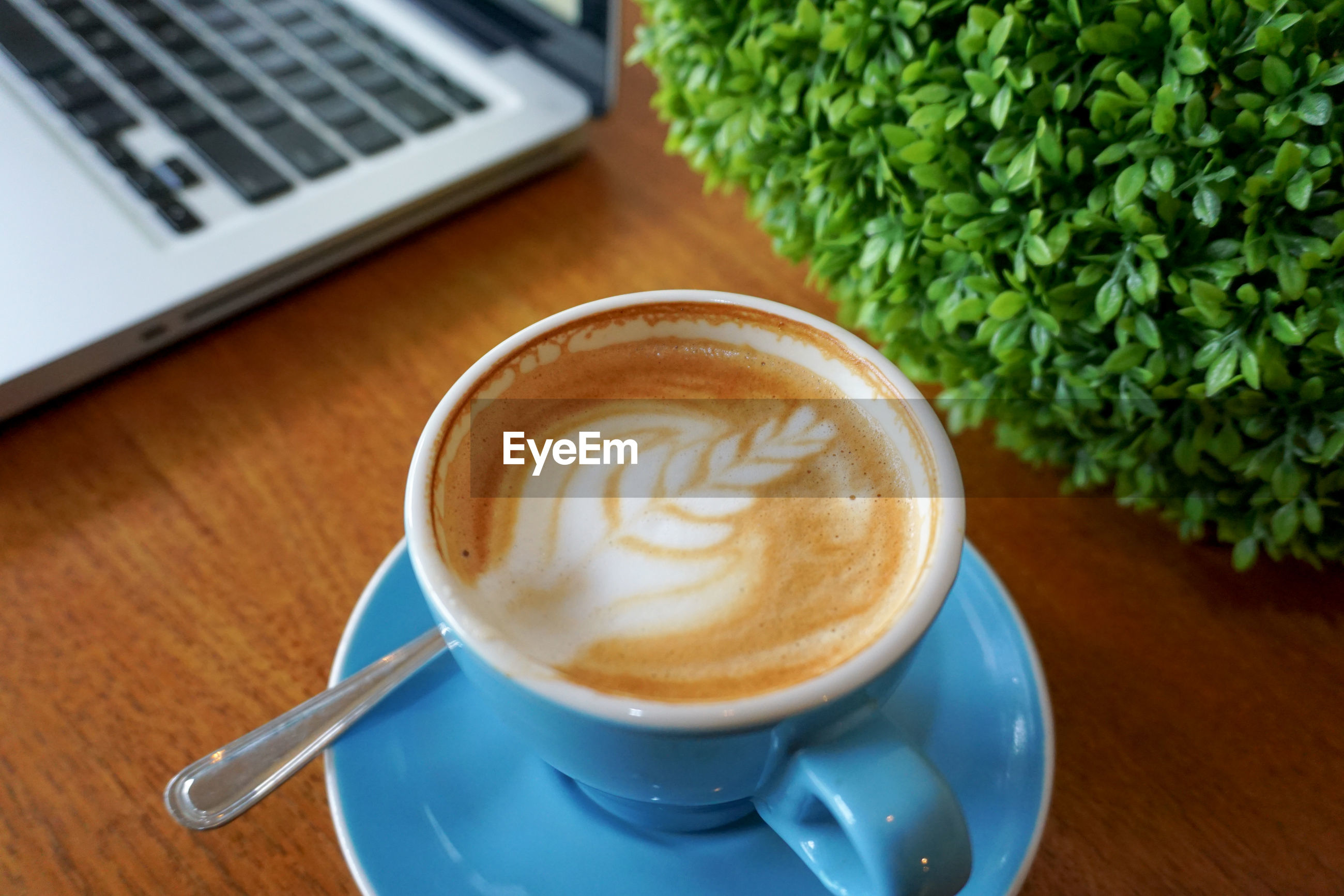 A glass of coffee next to the laptop