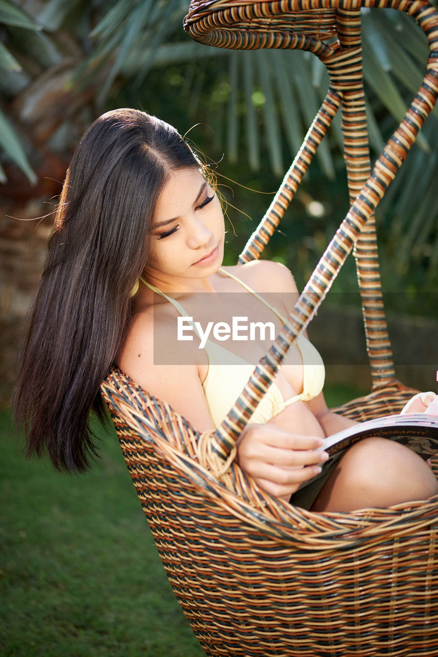 Young Woman Reading Book While Sitting In Wicker Swing