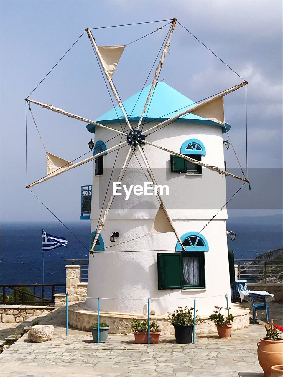 sky, nature, architecture, environmental conservation, wind power, built structure, building exterior, wind turbine, fuel and power generation, renewable energy, alternative energy, day, turbine, traditional windmill, building, no people, environment, cloud - sky, outdoors, blue