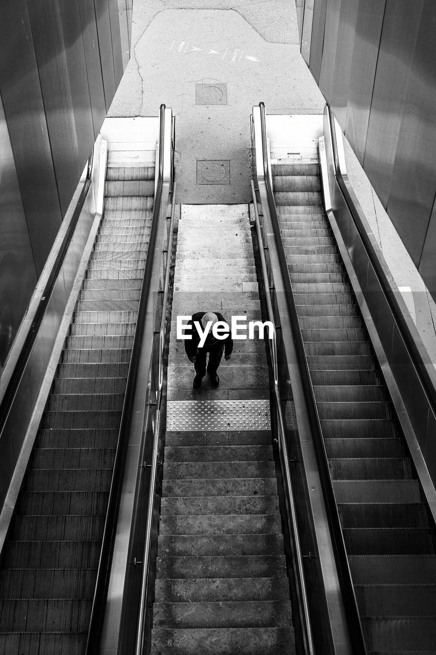 High Angle View Of Man Standing On Escalator