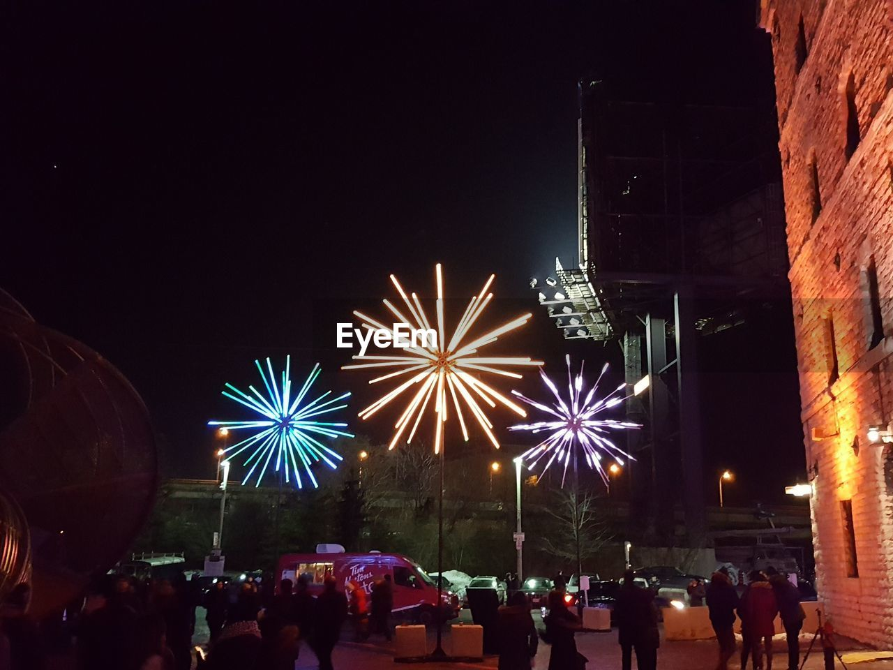 night, large group of people, real people, illuminated, arts culture and entertainment, celebration, lifestyles, men, leisure activity, women, built structure, event, firework display, firework - man made object, crowd, outdoors, architecture, building exterior, sky, people
