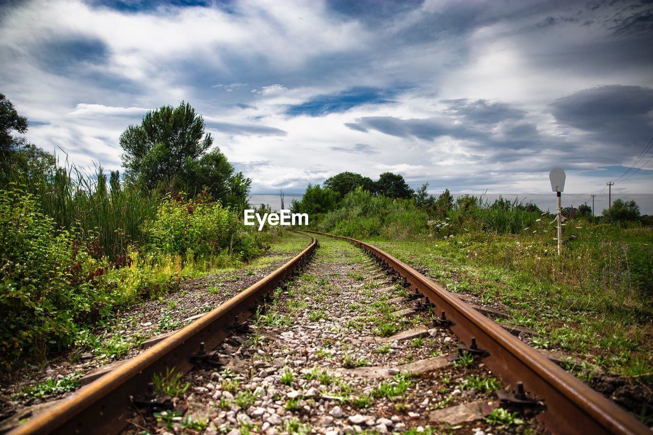 rail transportation, track, railroad track, plant, transportation, the way forward, direction, tree, cloud - sky, sky, diminishing perspective, nature, no people, vanishing point, day, growth, land, beauty in nature, outdoors, environment, gravel, long, parallel