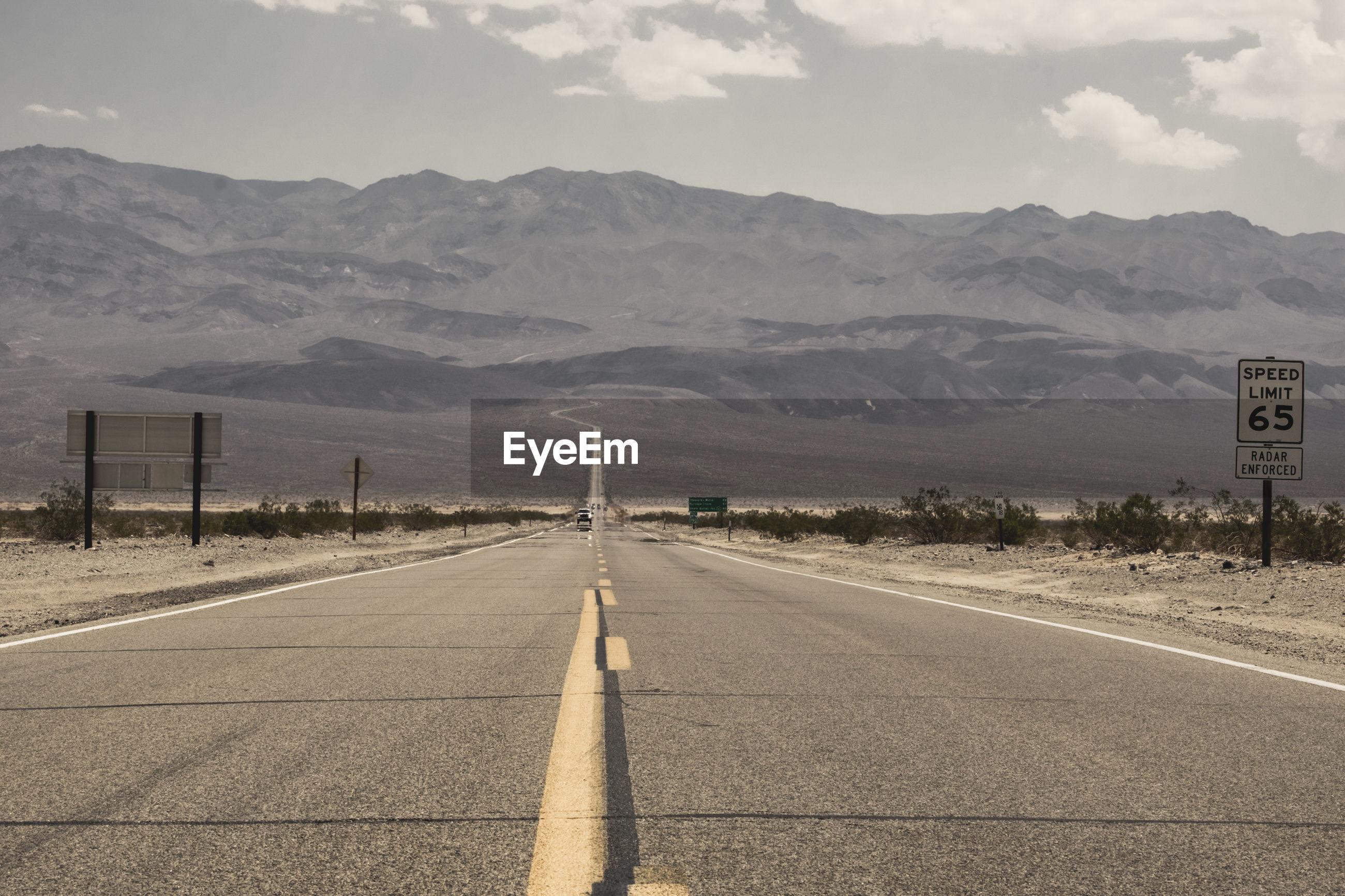 Empty road amidst land