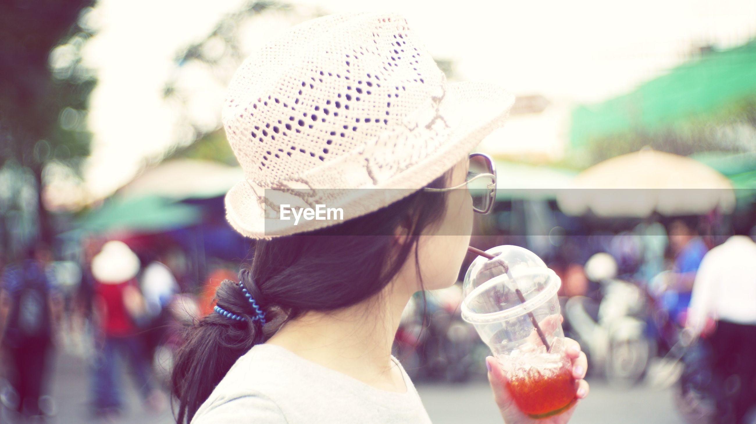 focus on foreground, lifestyles, leisure activity, rear view, person, casual clothing, men, selective focus, incidental people, waist up, standing, holding, street, hat, close-up, girls, outdoors, day