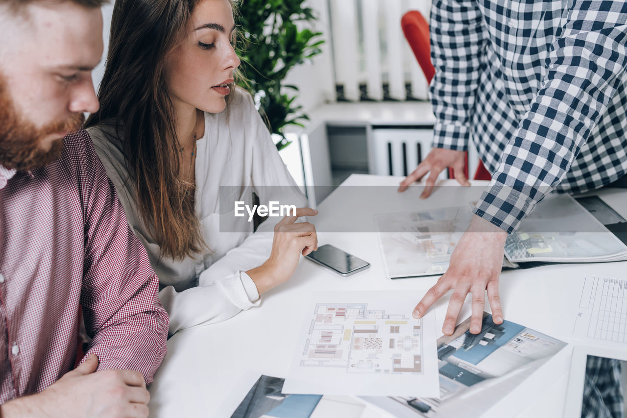 Young couple discussing over document while real estate agent explaining