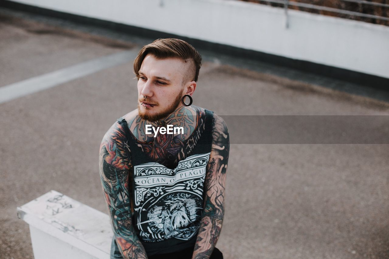 one person, real people, tattoo, young adult, lifestyles, beard, casual clothing, front view, high angle view, day, young men, outdoors, leisure activity