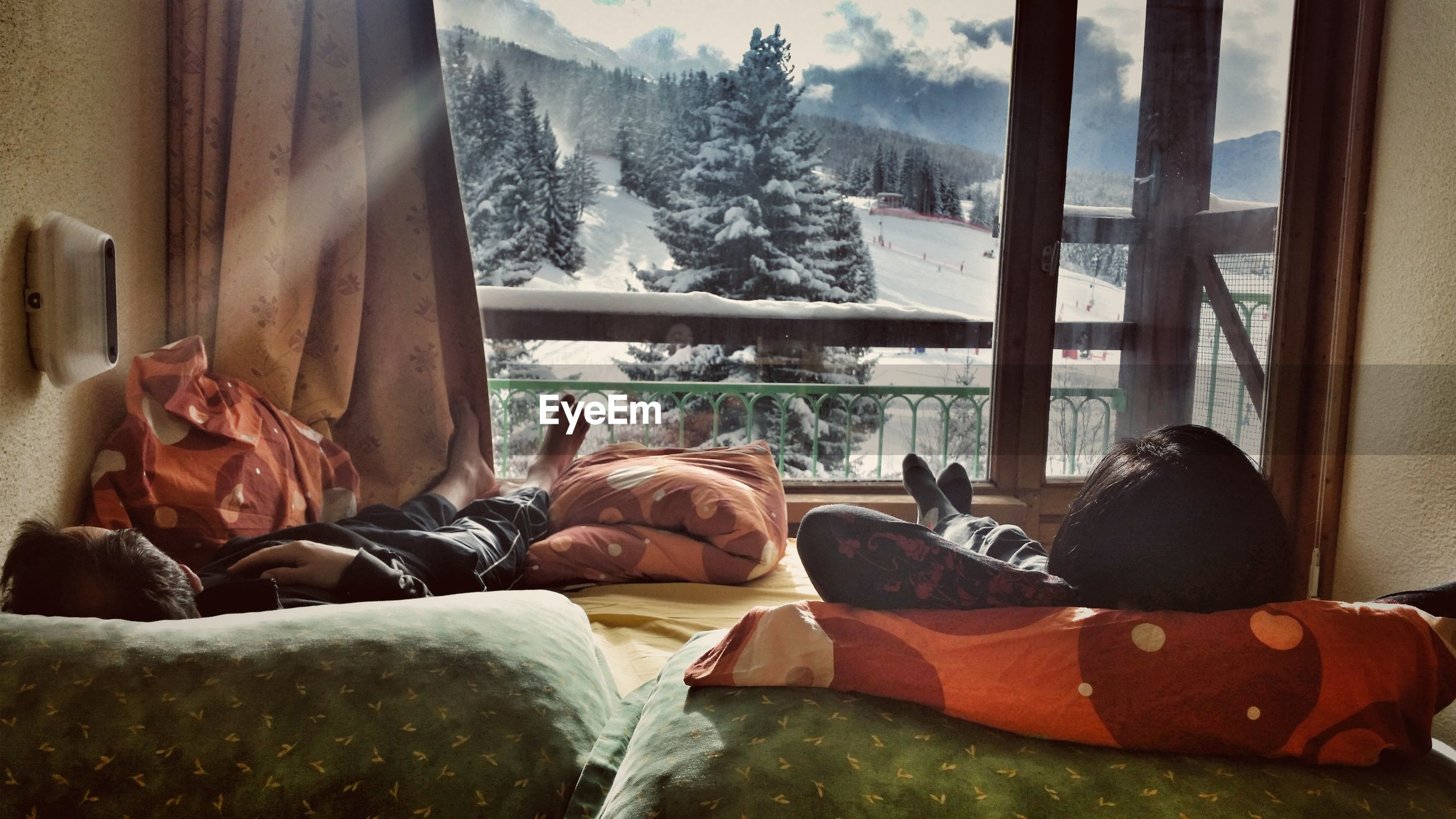 People lying down on bed against window at home during winter
