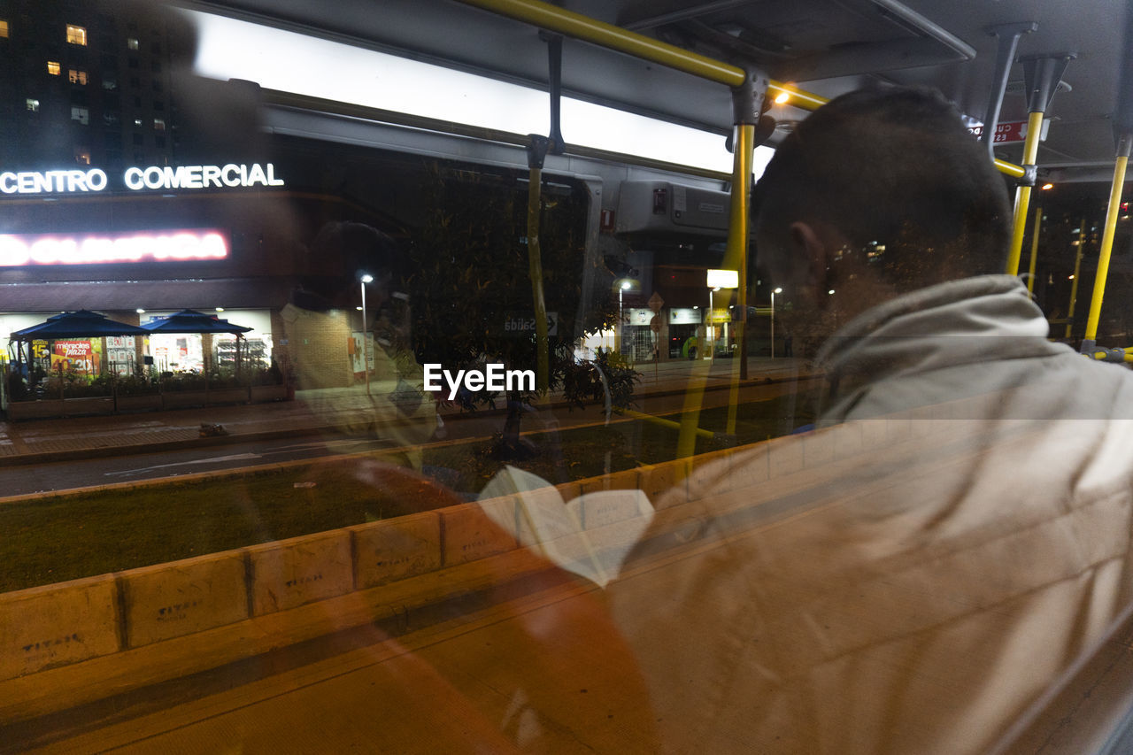 real people, illuminated, night, lifestyles, men, people, transparent, glass - material, public transportation, window, text, incidental people, leisure activity, indoors, reflection, architecture, business, communication, transportation
