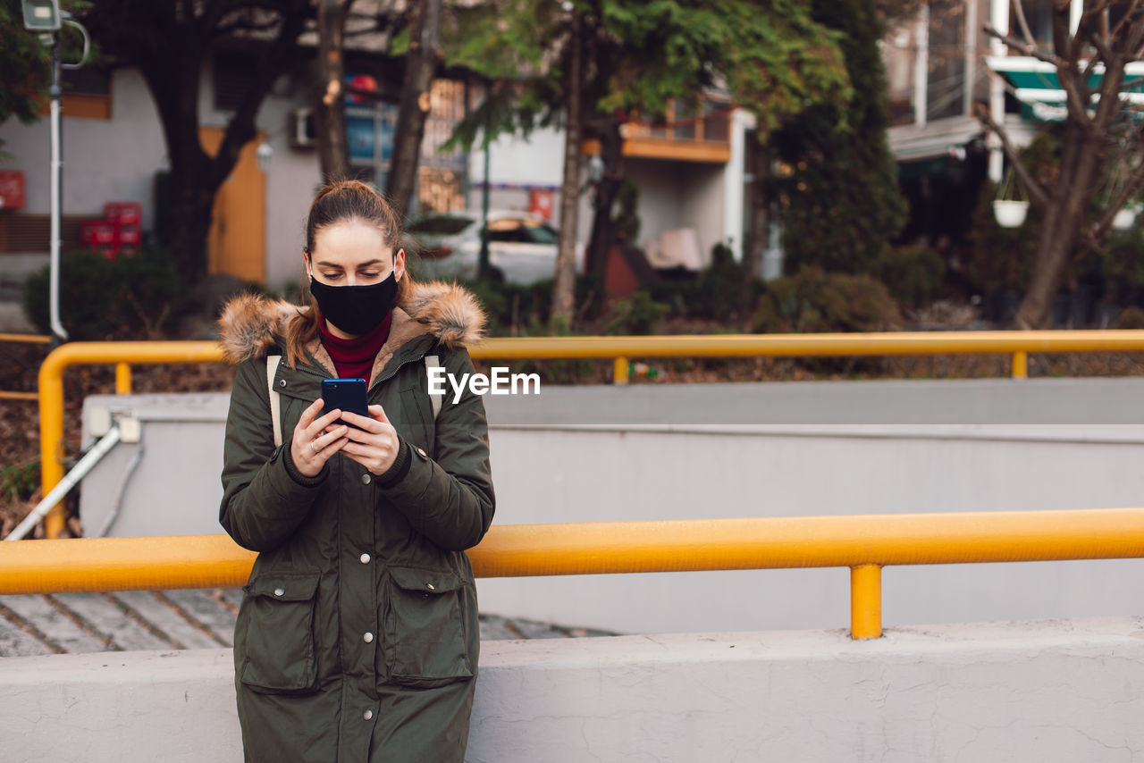 Young woman wearing mask using smart phone while standing outdoors