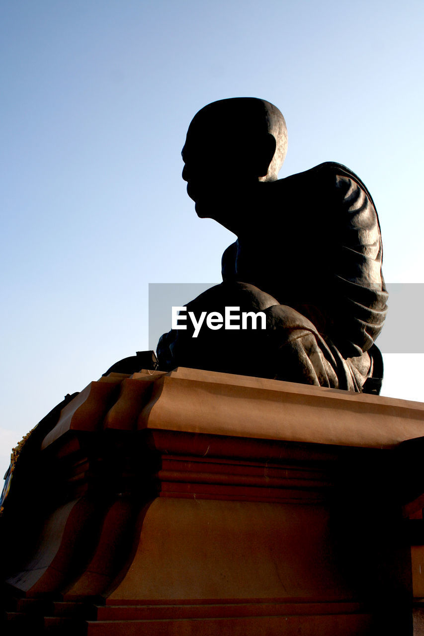 low angle view, clear sky, statue, day, sculpture, sky, outdoors, no people