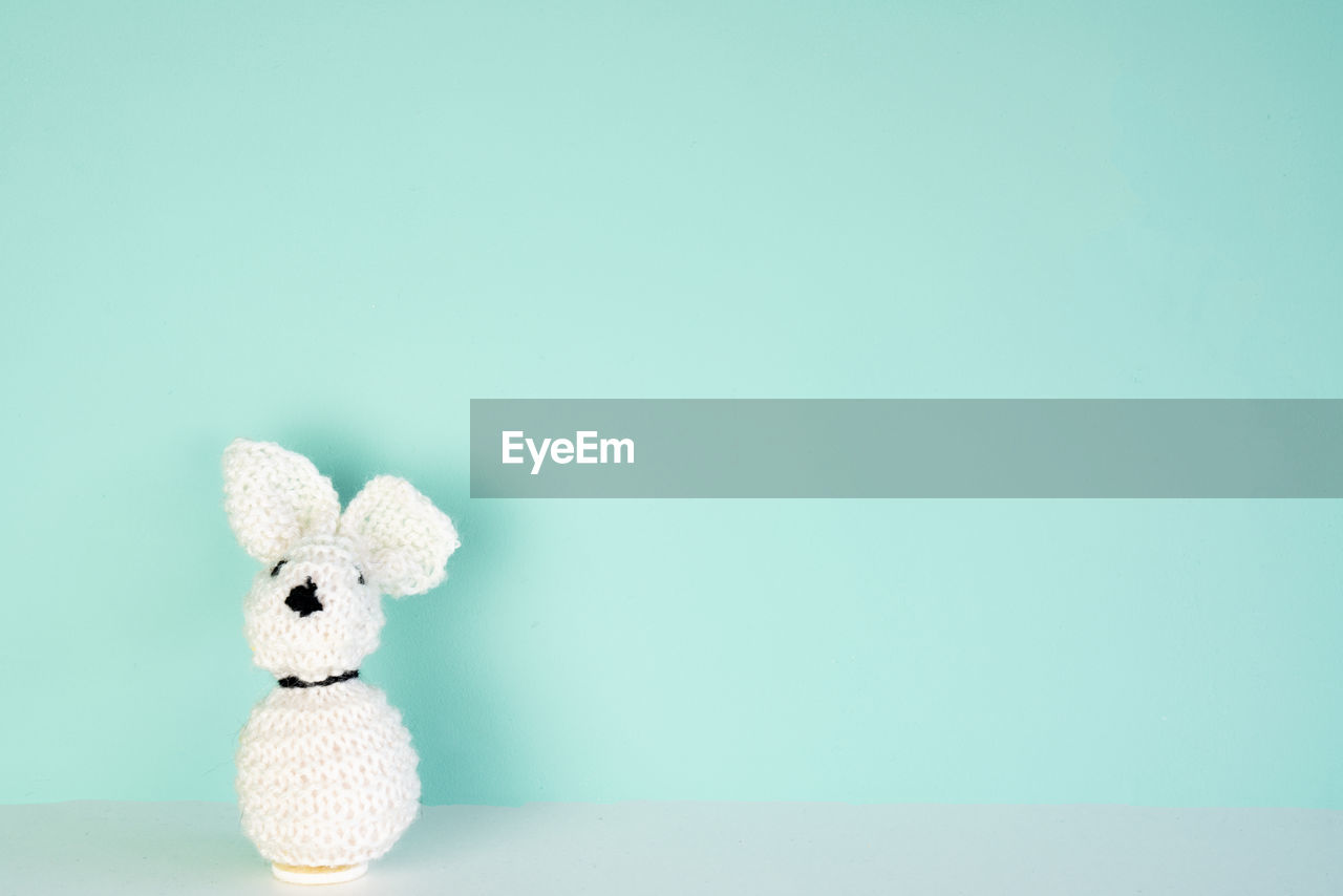 copy space, studio shot, indoors, colored background, stuffed toy, toy, still life, no people, cut out, blue, teddy bear, representation, animal representation, single object, close-up, blue background, wall - building feature, art and craft, white color, softness, turquoise colored