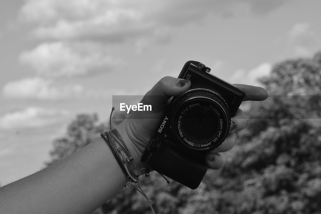 human hand, human body part, holding, real people, sky, cloud - sky, camera - photographic equipment, one person, leisure activity, photography themes, outdoors, focus on foreground, day, photographing, technology, lifestyles, low angle view, close-up, nature, digital single-lens reflex camera, people