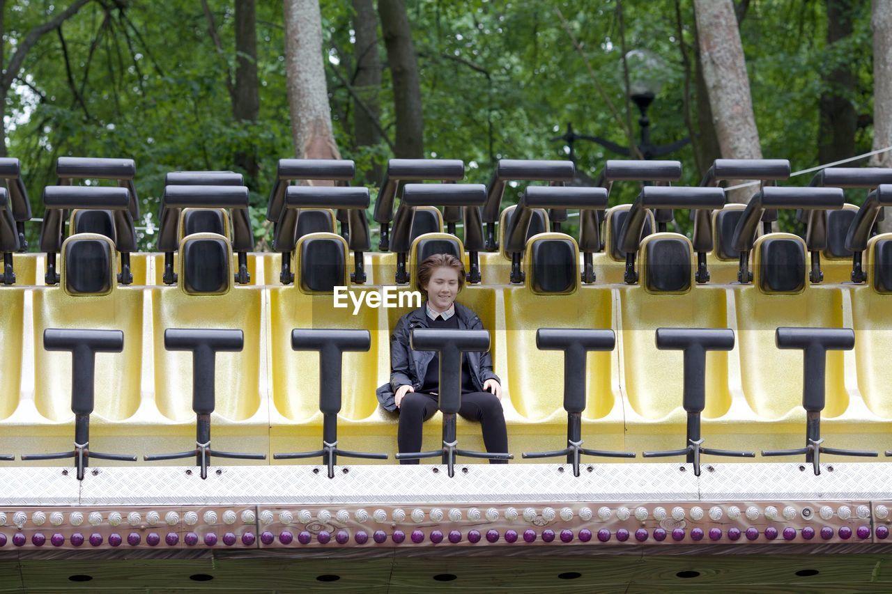 Girl sitting on amusement park ride against trees