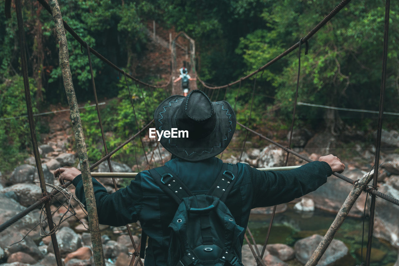 tree, forest, land, weapon, day, plant, real people, nature, one person, gun, rear view, men, woodland, outdoors, security, safety, unrecognizable person, clothing, hunter