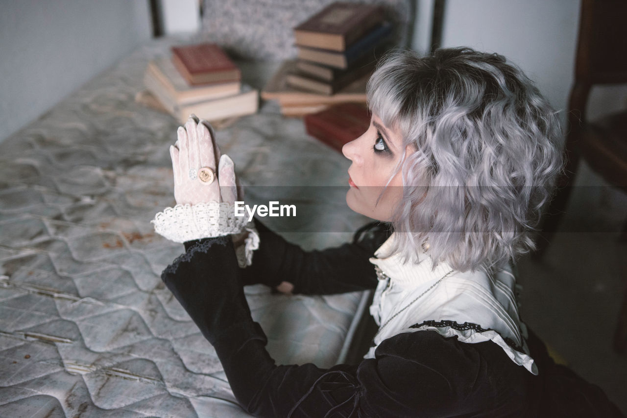High angle view of woman praying at home