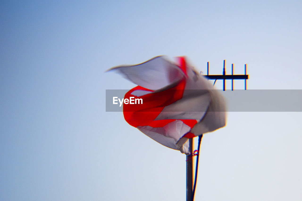 sky, clear sky, flag, nature, low angle view, red, wind, no people, copy space, day, patriotism, blue, environment, waving, pole, emotion, outdoors, textile, shape, national icon