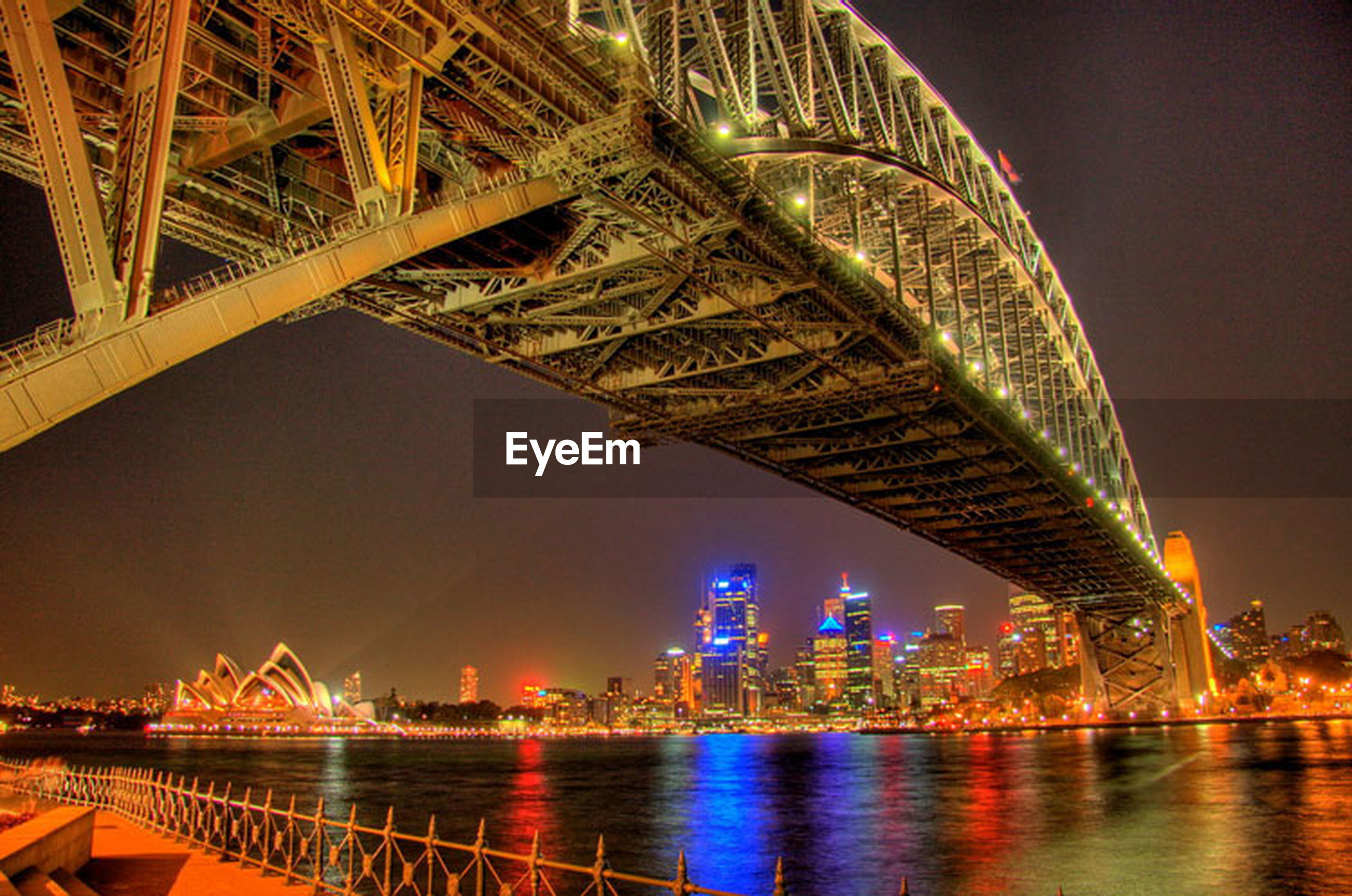 illuminated, night, architecture, built structure, water, waterfront, river, bridge - man made structure, connection, city, reflection, building exterior, engineering, sky, travel destinations, low angle view, bridge, famous place, capital cities, no people