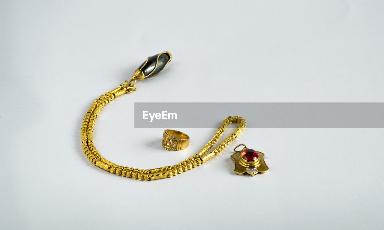 HIGH ANGLE VIEW OF GOLD COLORED ON WHITE BACKGROUND
