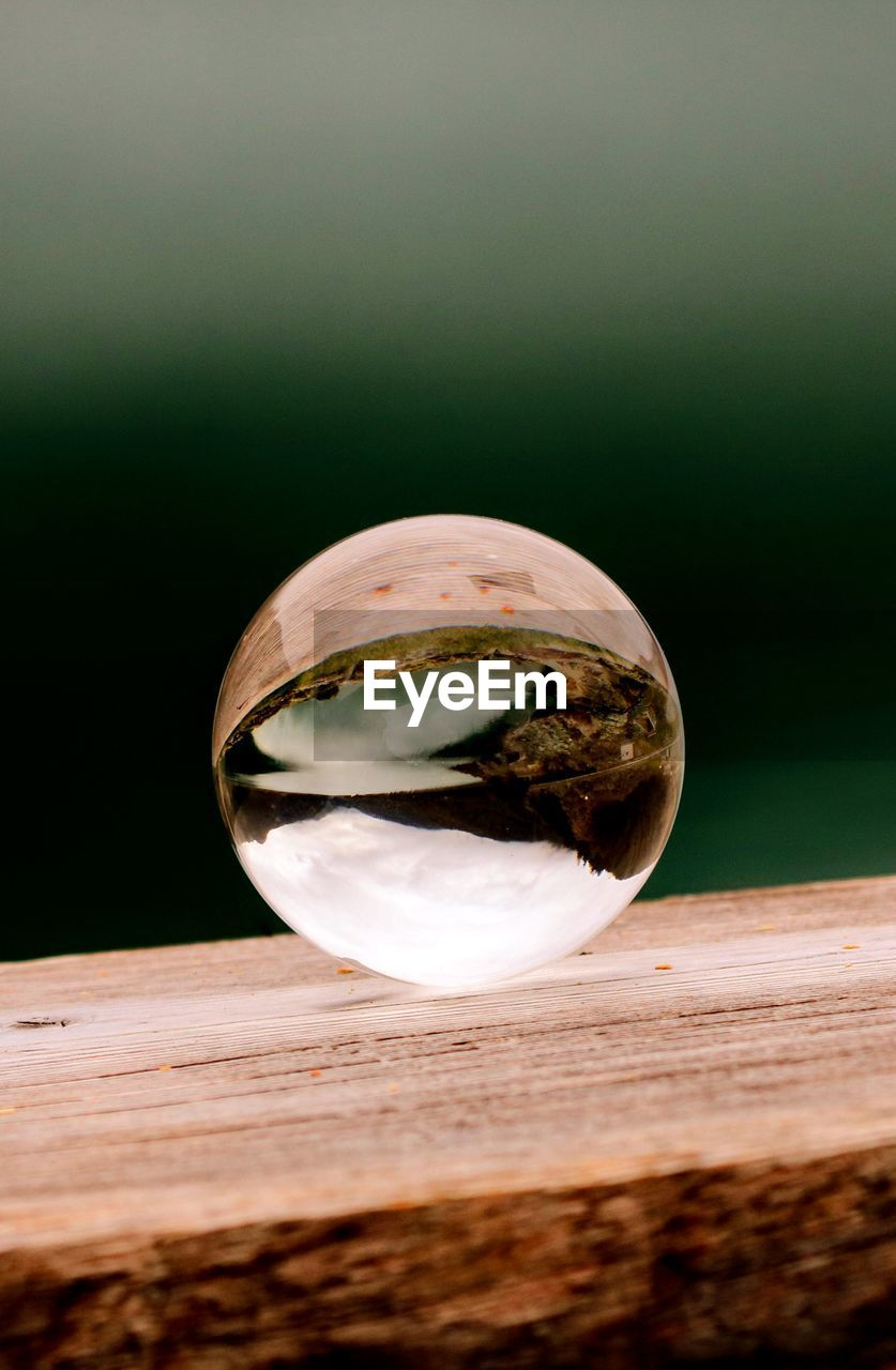 CLOSE-UP OF GLASS OF CRYSTAL BALL ON WOODEN SURFACE