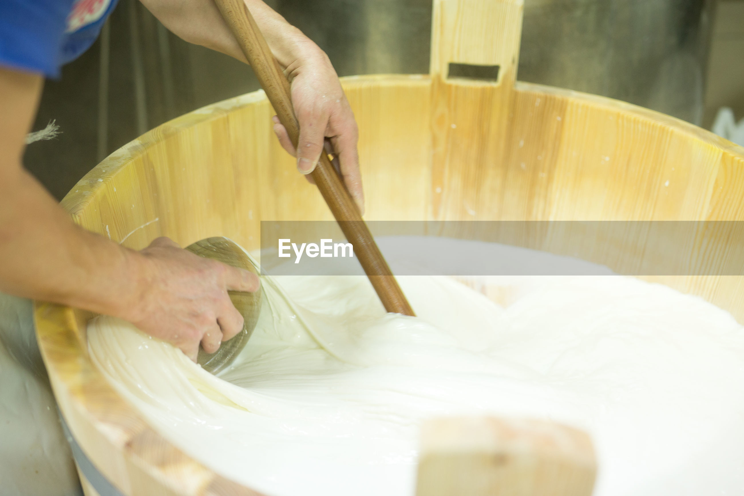 High angle view of worker mixing mozzarella cheese with ladle in wooden container at factory