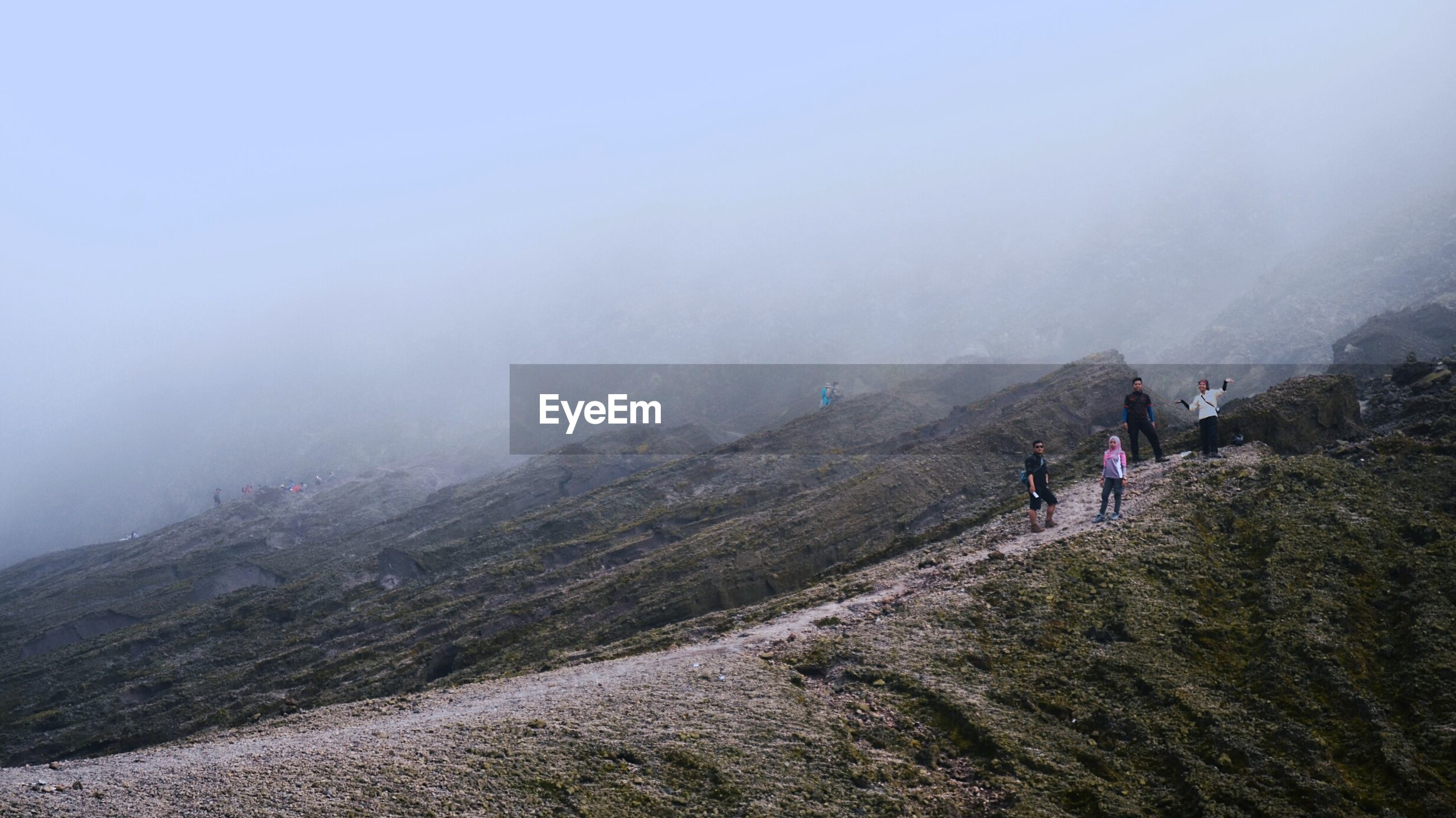 Friends on mountain during foggy weather