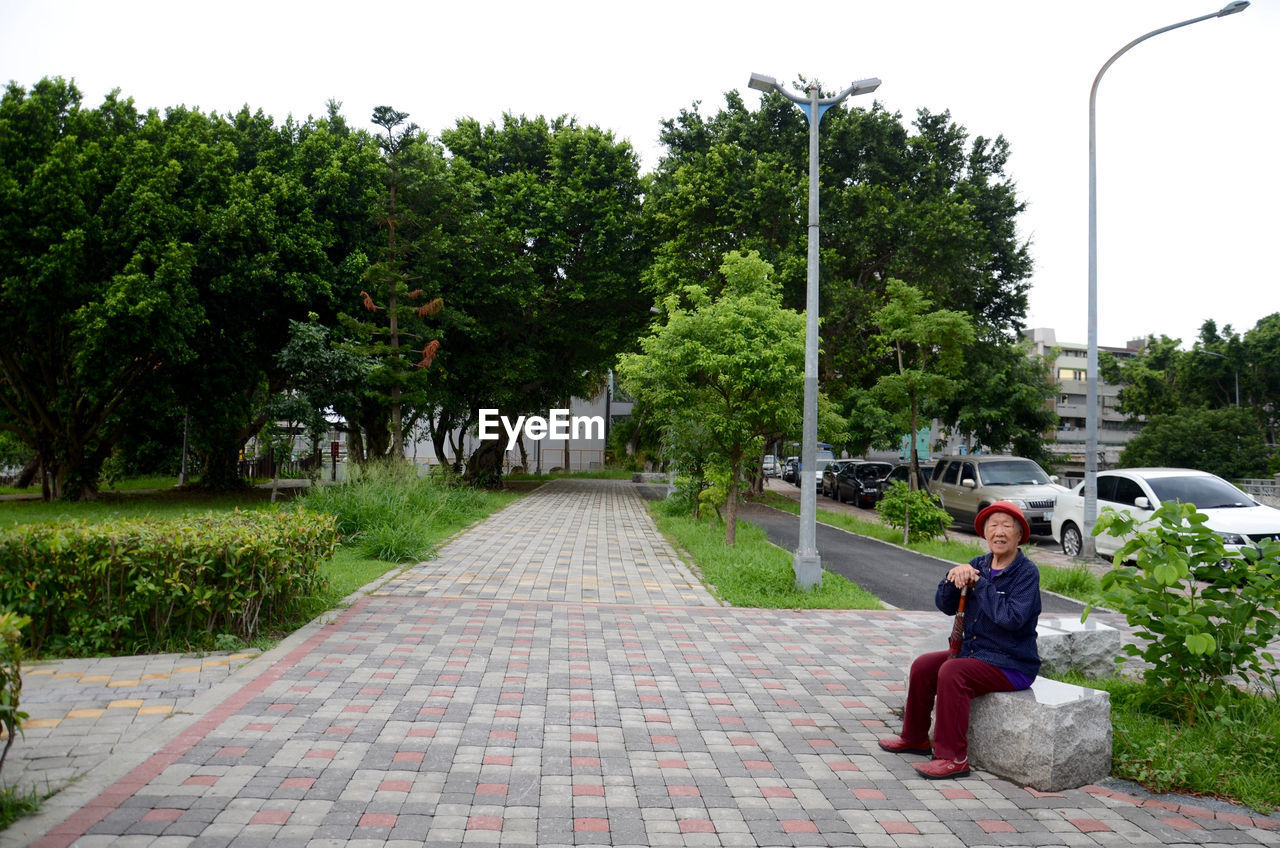 Senior Woman Sitting On Stone Bench At Park