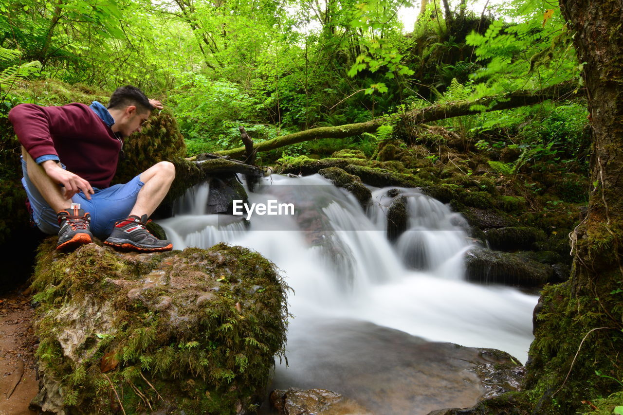 Young man sitting on rock by waterfall in forest