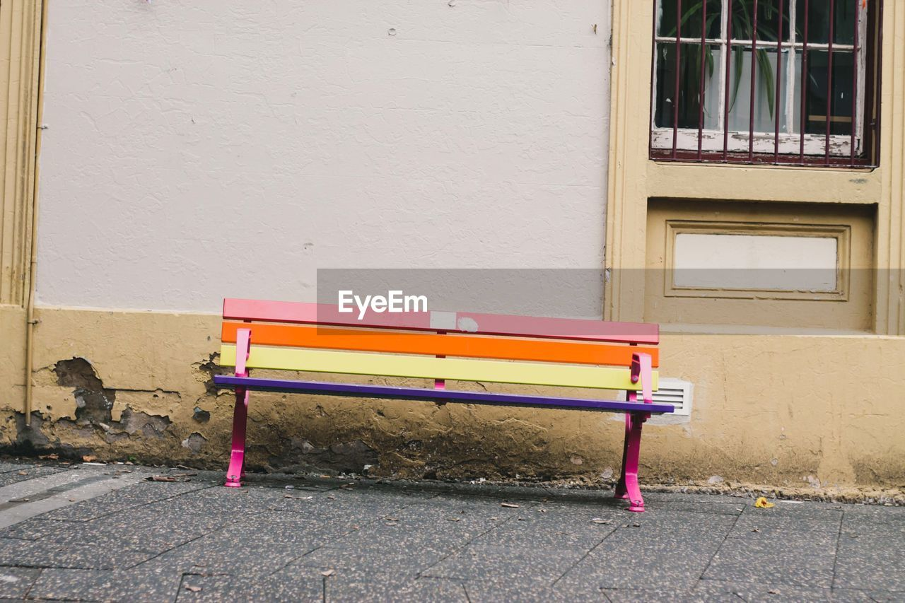 seat, building exterior, architecture, empty, built structure, no people, bench, absence, wall - building feature, day, building, window, chair, pink color, outdoors, city, wall, street, multi colored, footpath, purple