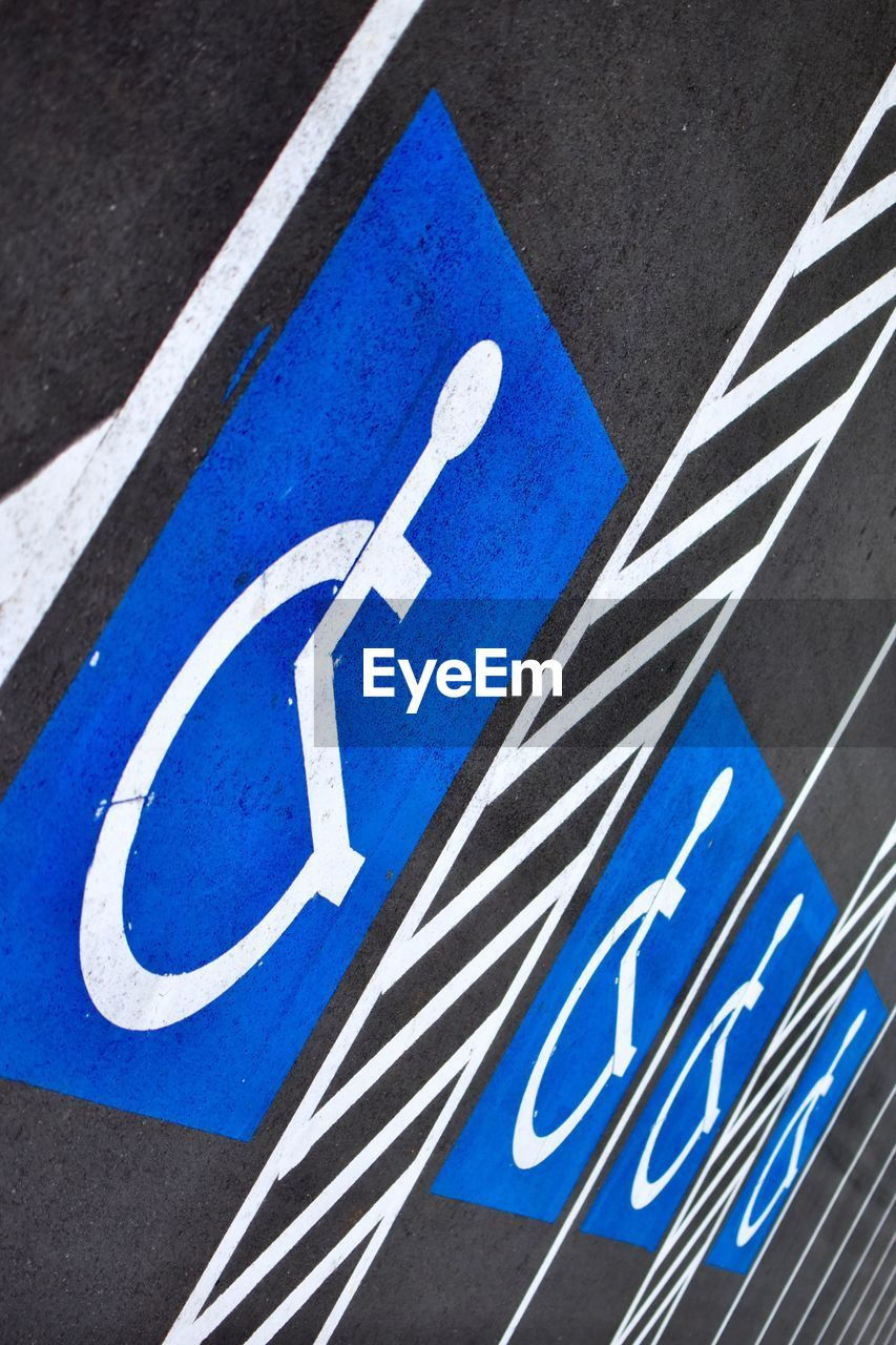 sign, road, blue, communication, white color, transportation, symbol, no people, road sign, city, road marking, day, marking, guidance, street, close-up, human representation, architecture, high angle view, outdoors