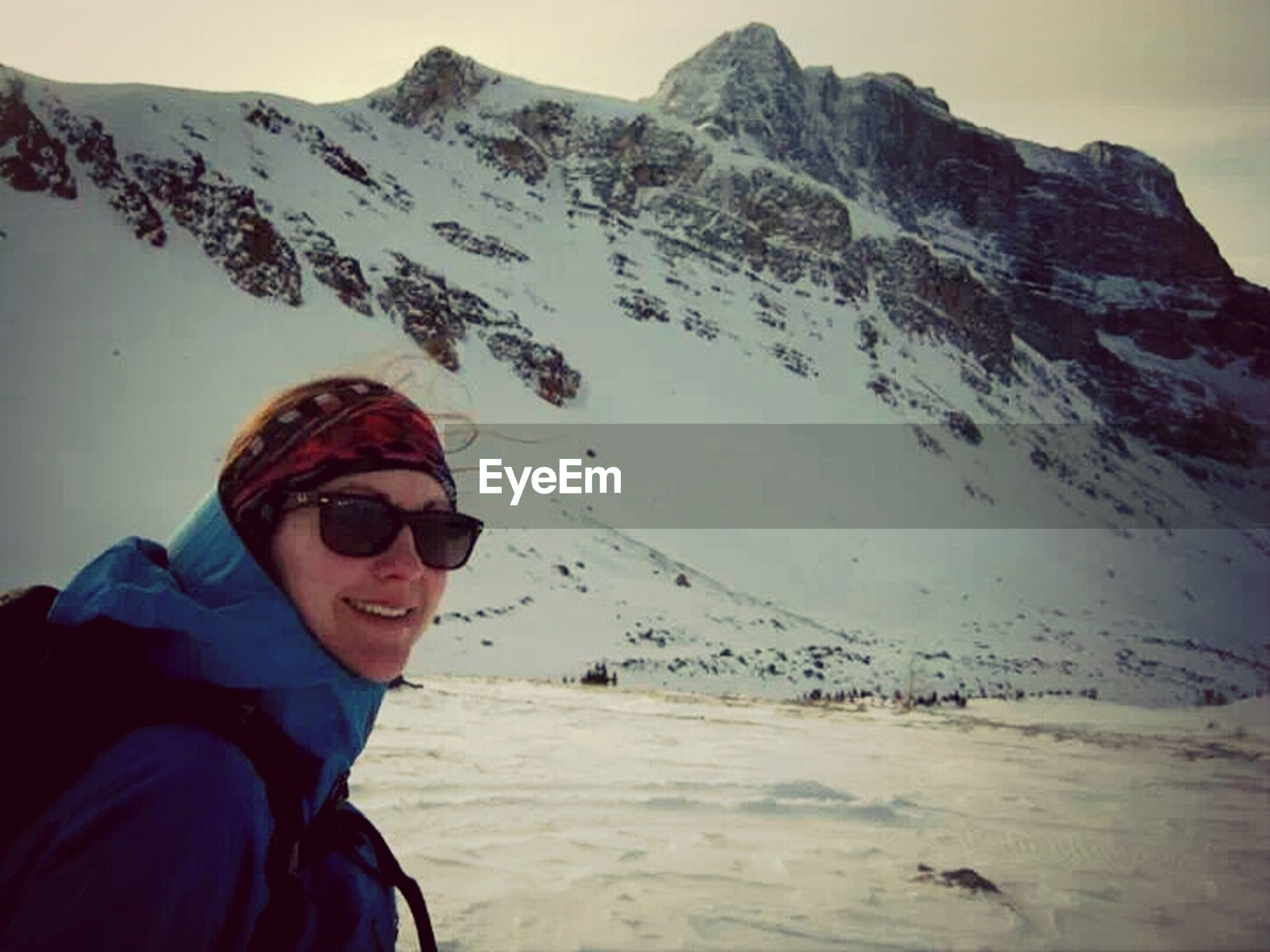 snow, winter, cold temperature, lifestyles, leisure activity, mountain, season, warm clothing, young adult, person, looking at camera, portrait, young men, mountain range, casual clothing, smiling, vacations, weather