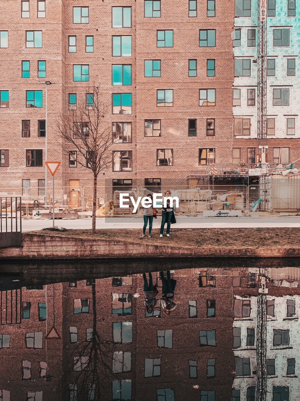architecture, built structure, building exterior, building, window, city, reflection, residential district, men, two people, water, real people, people, day, nature, outdoors, wall, city life, tree, canal, apartment