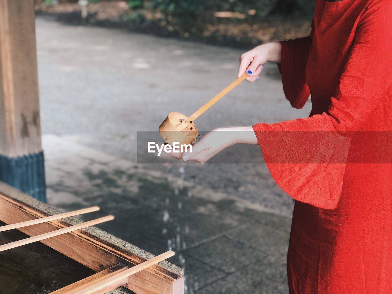 Midsection Of Woman Pouring Water Using Bamboo Ladle While Washing Hand At Shrine