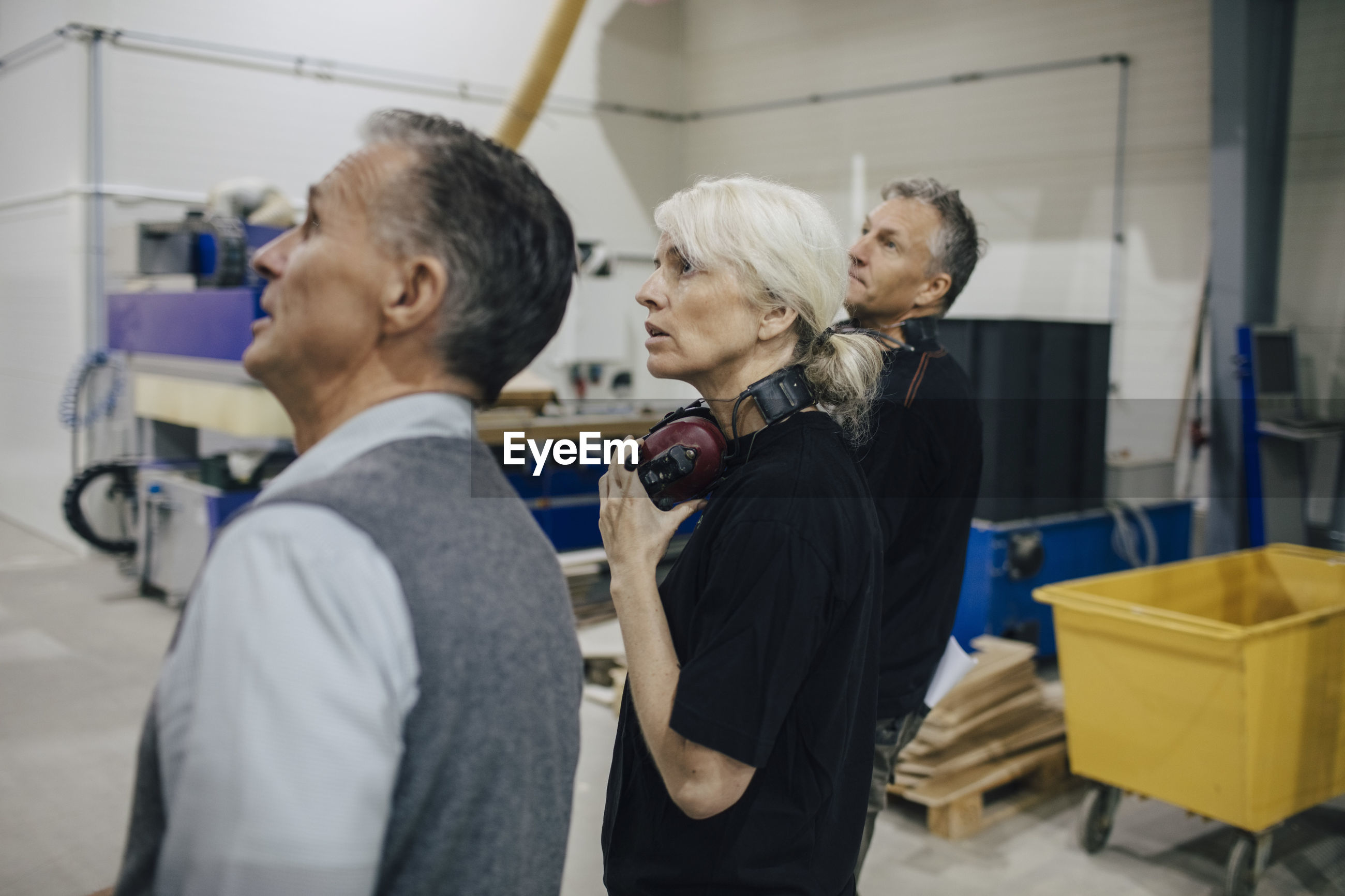 Business people discussing with colleagues while walking in industry